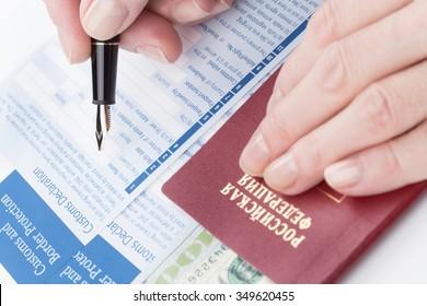female hand  fills customs declaration russian travel passport