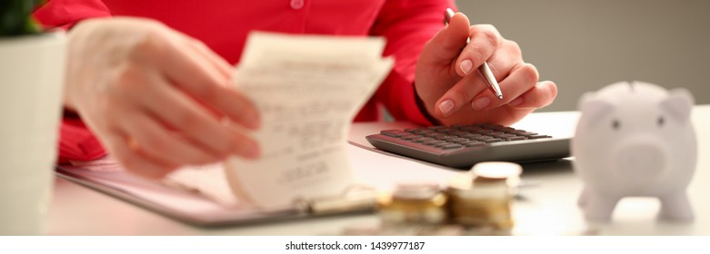 Female hand financial inspector push key butoon on gray calculator. Makes calculation costs turning over in hands paper checks for month. Family budget planning concept.
