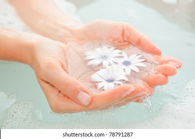 female hand and flower in water