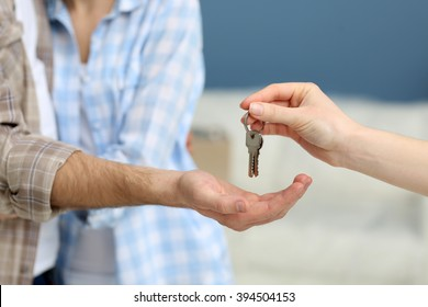 Female hand giving keys from new apartment to male hand on blurred background