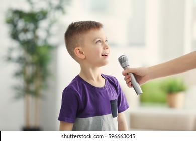 Female hand giving microphone to cute little boy at home