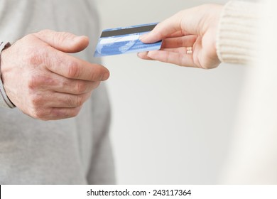 Female hand giving a plastic card to senior male hand