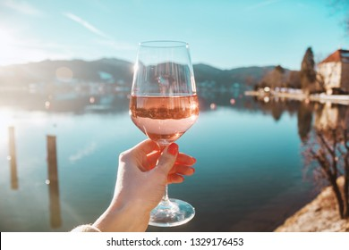 Female hand with glass of wine. Cozy pier on the coast of the lake Tegernsee. Alpine mountains in Bavaria (Bayern). Mountain view, beautiful landscape in Germany. Adventure in Europe (travel photo).