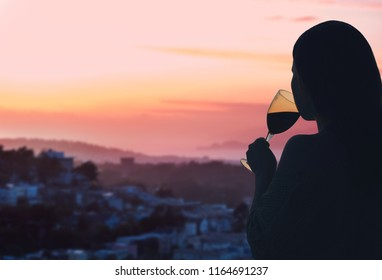 Female hand with glass of wine on  San Francisco city background. Service on the roof of the restaurant