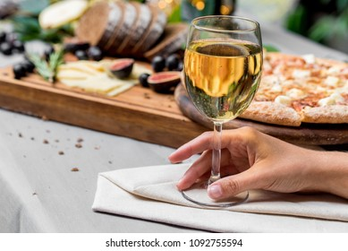 Female hand with glass of wine,pizza in background