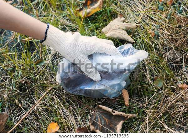 female hand in glove. cleaning plastic and garbage in the forest. ecological problems. plastic bottles and bags