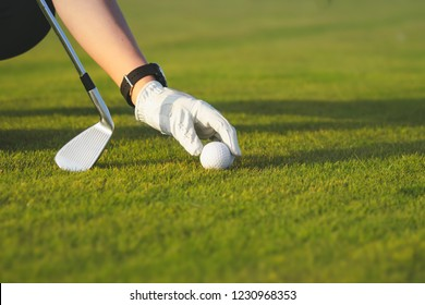 female hand in glove placing golf ball on green at golf course