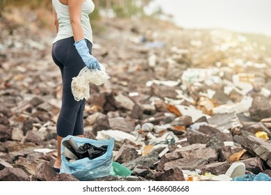 Female hand in gloves holds plastic garbage on the background of sea coast.