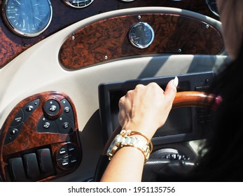 A female hand with a gold watch holds the steering wheel located on the dashboard of a cruise yacht