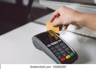 Female hand with golden bank card using the terminal for payment.