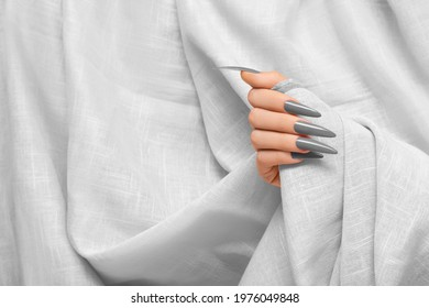 Female hand with gray stiletto nail design. Long nail polish manicure. Woman hand on white fabric background.