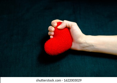 Female hand grips a red heart tightly