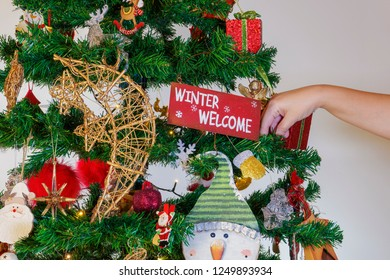 Female hand hanging seasonal ornaments on a Christmas tree with lights.Festive colorful decorations before an illuminated artificial Christmas tree with winter welcome message hanging from a brunch.