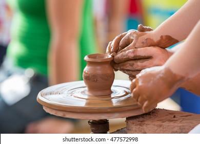 Female hand helping to make ceramic jug on a wheel children's hands.
