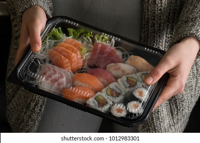 Female hand hold assorted sushi take away plastic package
