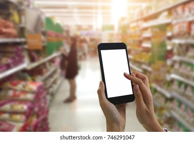 Female hand hold black smartphone at supermarket and checking shopping list