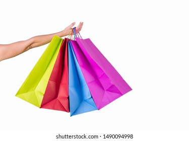 Female hand hold color paper bags isolated on white background