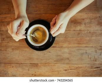 Female hand hold a cup of black coffee on wooden background, top view