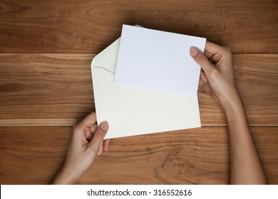 A female hand hold an envelope and post card on the wood desk, top view at the studio.
