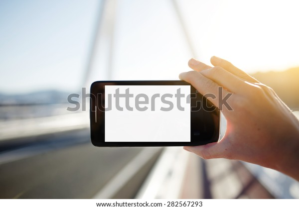 Female hand hold smart phone with blank copy space area for your text message or content,tourist woman holding cell phone while taking a photograph of landscape in summer travel,empty digital screen