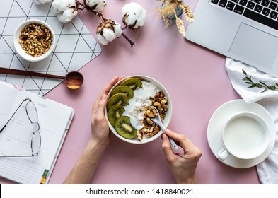 Female hand hold spoon over healthy breakfast concept bowl enjoy detox morning meal on work table background with laptop milk, woman eat natural granola nutrition detox food in home office, top view