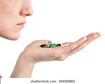 Female hand holding all sorts of pilss and tablets close to her mouth on white background