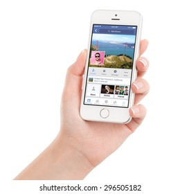 Female hand holding Apple Silver iPhone 5S with Facebook application on the screen. Facebook is an online social networking service. Isolated on white background. Varna, Bulgaria - February 02, 2015.