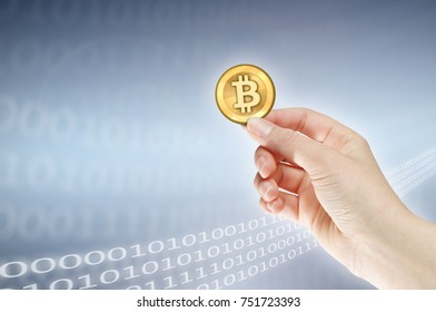 Female hand holding bitcoin against binary background