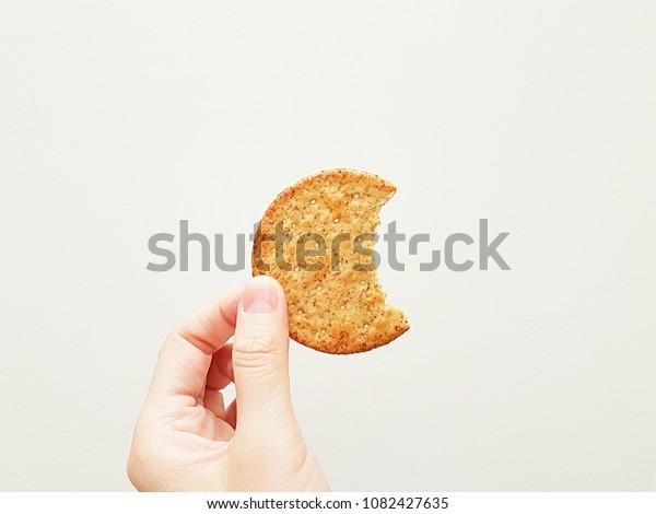 Female hand holding bite of around wheat cracker isolated on white background