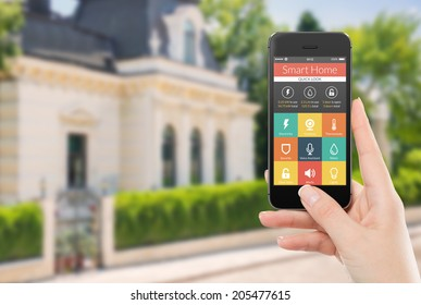 Female hand holding black mobile smart phone with smart home application on the screen. Blurred house on the background. For access to all of the controls of your house and caring of home security.