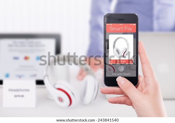 Female hand holding black mobile smart phone with nfc smart pay application.  Blurred store with seller and gadgets on the background. Purchase of headphones by fingerprint scanning in smart pay app.