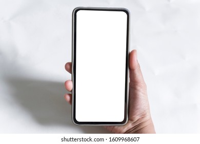 Female hand holding black smart phone with white screen on white background.
