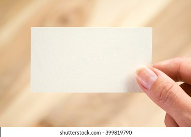 Female hand holding blank business card.