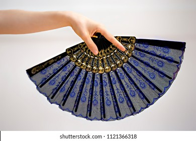 Female hand holding a blue fan