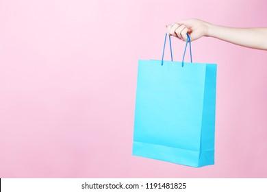 Female hand holding blue shopping bag on pink background