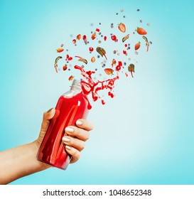 Female hand holding bottle with red splash summer beverage: smoothie or juice and berries at blue background.