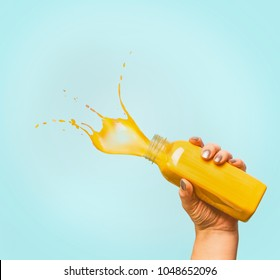 Female hand holding bottle with yellow splash summer beverage: smoothie or juice at blue background, copy space