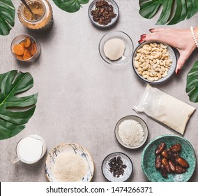 Female hand holding bowl with cashew on concrete background with vegan gluten-free cake ingredients: non dairy milk, almond flour, Coconut cream and milk, agar agar and dried fruits . Top view