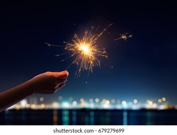 Female hand holding a burning sparkler