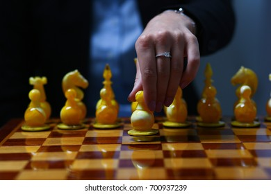 Female hand holding a business woman holding a chess piece. Makes the first move in the business strategy