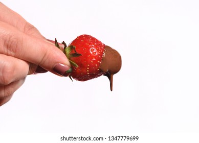 Female hand holding chocolate-dipped strawberry on the white background. Melted chocolate and strawberry