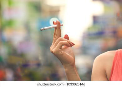Female hand holding cigarette with nails painted on colourful background