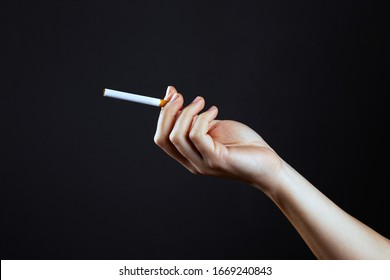 female hand holding a cigarette on a dark background close-up.