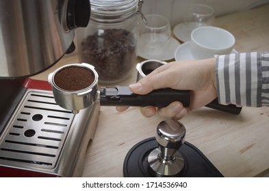 female hand holding coffee holder near coffee machine at home.