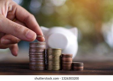 Female hand holding coin set money to success , Saving and growing business concept, selective and soft focus.