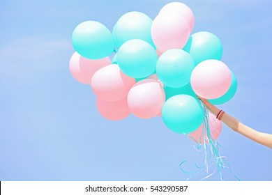 Female hand holding colorful balloons against blue sky