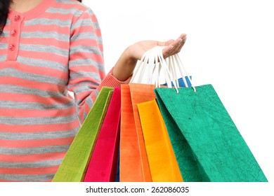Female hand holding colorful shopping bags against white
