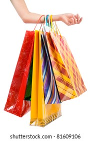 Female hand holding colorful shopping bags on white