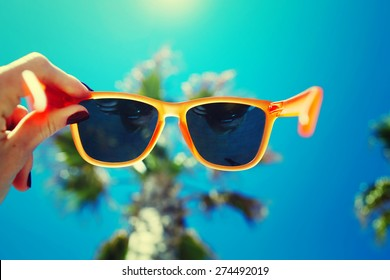 Female hand holding colorful sunglasses against palm tree and blue sunny sky, summer vacation holidays concept, first person shot, looking though glasses, filtered image