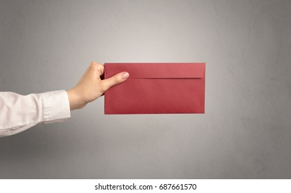 Female hand holding coloured and white envelope with empty wall background